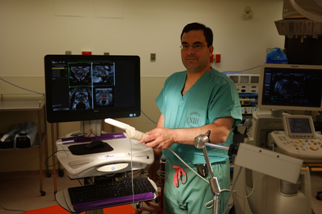 Peter Pinto, M.D., in green scrubs in operating room, holding white rectal probe, posing in front of UroNav readout computer screen, which shows 4 images of prostate fused by the UroNav software.
