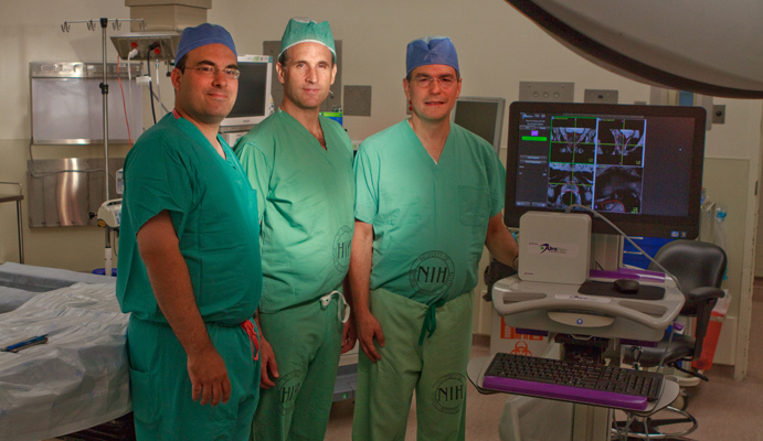 Three male physicians, all wearing green surgical scrubs and blue or green head covers, pose in an operating room with a UroNav device, which resembles a computer workstation on a cart.